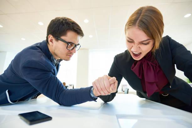 leistungsstarke business-dame armdrücken zu gewinnen - armdrücken stock-fotos und bilder