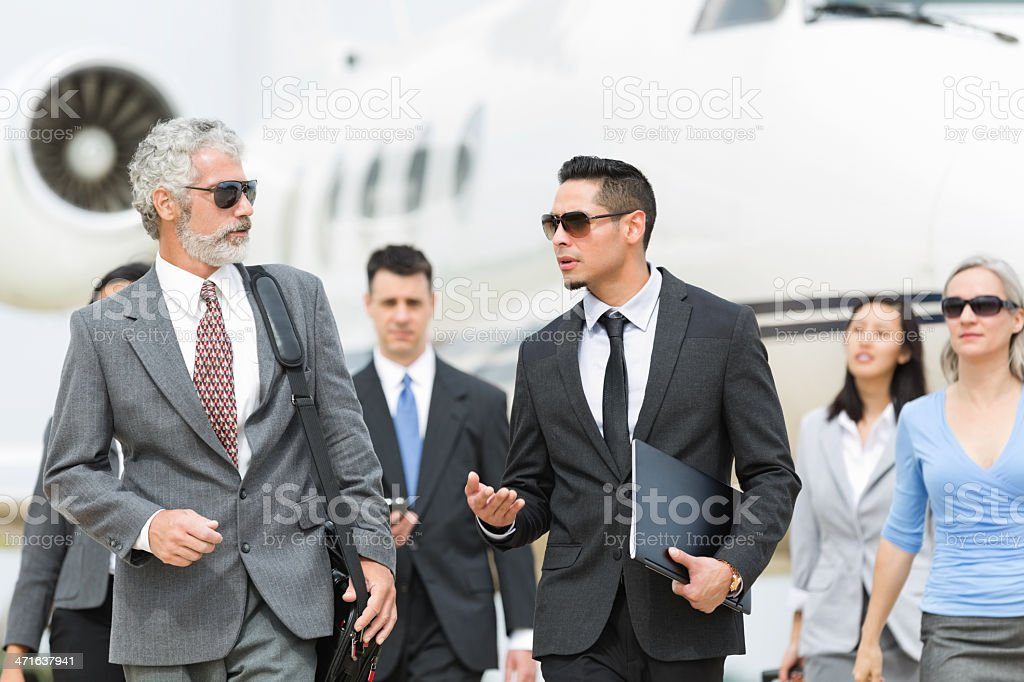 Powerful business team deboarding private corporate jet stock photo
