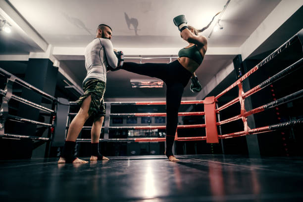 powerful caucasian boxer girl in sportswear, with bandage on feet and boxing gloves on hands practicing with trainer in ring. - color intensity stock pictures, royalty-free photos & images