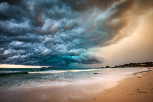 Powerful dramatic storm cell over ocean beach with golden light, Australia