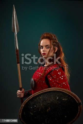 Side view of powerful female fighter in armor keeping spear and shield and posing on isolated background in studio. Young red haired woman looking at camera. Female hero fighting in combat.