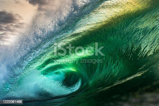 Powerful green and gold wave breaking heavily in ocean over reef and rock