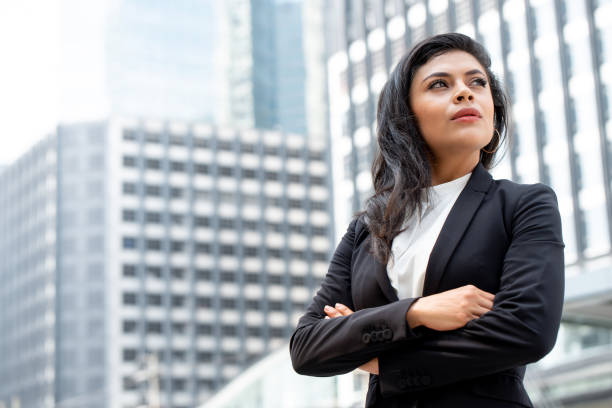 Powerful Latin businesswoman leader standing with arm crossed Powerful Latin businesswoman leader standing with arm crossed in city office building background arbiter stock pictures, royalty-free photos & images