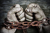 Dirty powerful male hands clenched into fists and chained with old rusty thick chain on the wooden boards. Unfreedom concept.