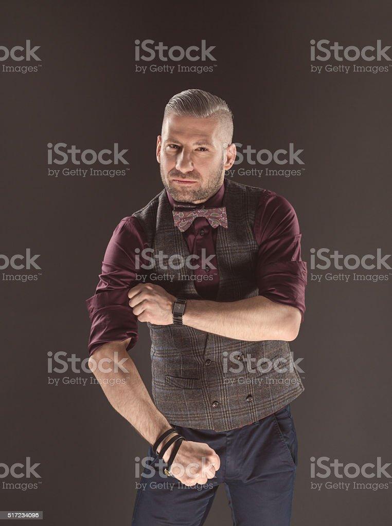 Powerful man wearing bow tie and tweed vest Powerful bearded man wearing tweed vest, shirt and bow tie, looking at camera. Dark tone, black background. Adult Stock Photo