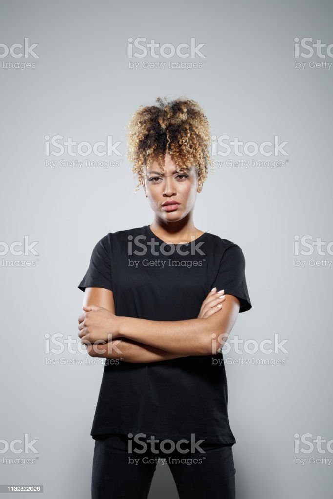 Powerful mid adult woman standing arms crossed Portrait of powerful mid adult woman standing arms crossed. Determined female protester is wearing black clothing. She is supporting Me Too movement. 30-34 Years Stock Photo