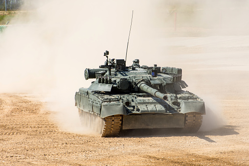 Powerful military tank rides at a high speed along the dusty field