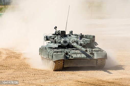 istock Powerful military tank rides at a high speed along the dusty field. 1047478726