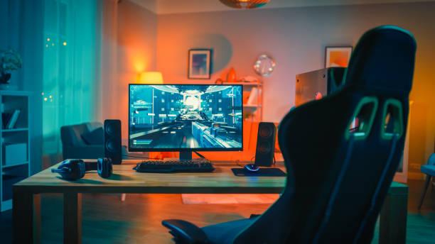 画面上の一人称シューティングゲームと強力なパーソナルコンピュータゲーマーリグ。モニターは自宅のテーブルの上に立っています。モダンなデザインの居心地の良い客室は、暖かくネオ� - ゲーム ヘッドフォン ストックフォトと画像