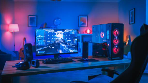 Leistungsstarke Personal Computer Gamer Rig mit First-Person Shooter Spiel auf dem Bildschirm. Monitor steht zu Hause auf dem Tisch. Gemütliches Zimmer mit modernem Design ist Lit mit rosa Neon Licht. – Foto