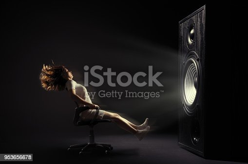 The powerful sound set back an office cheir with young woman.