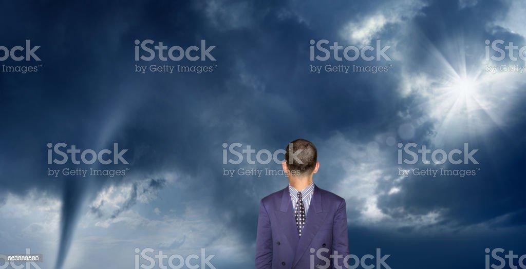 Powerful tornado with sunbeam and businessman stock photo