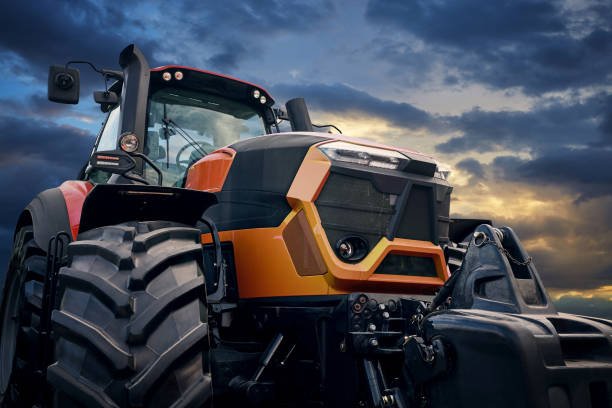 Powerful tractor on sunset background stock photo