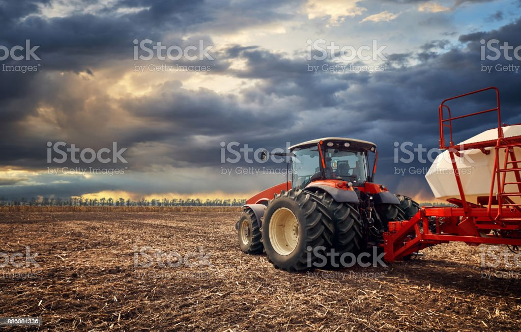 A powerful tractor works in the field stock photo