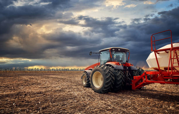 A powerful tractor works in the field Tractor working on the farm, a modern agricultural transport, a farmer working in the field, fertile land, tractor on a sunset background, cultivation of land, agricultural machine agricultural machinery stock pictures, royalty-free photos & images