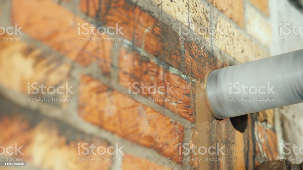 A diamond-tipped drill drills a hole in a brick wall