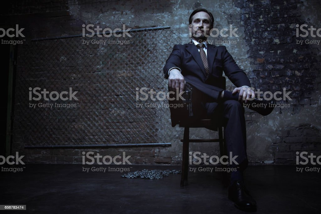 Powerful world class criminal sitting on his throne stock photo