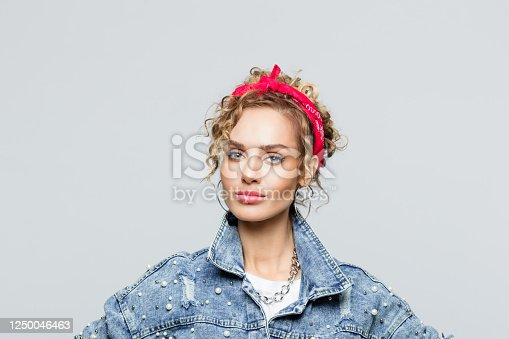 Portrait of blond curly hair confident young woman wearing white t-shirt, denim jacket and red bandana, looking at camera. Studio shot on grey background.