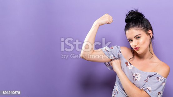 Powerful young woman in a success pose on a solid background