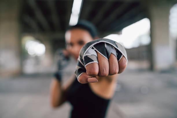 Powerful young woman punching stock photo