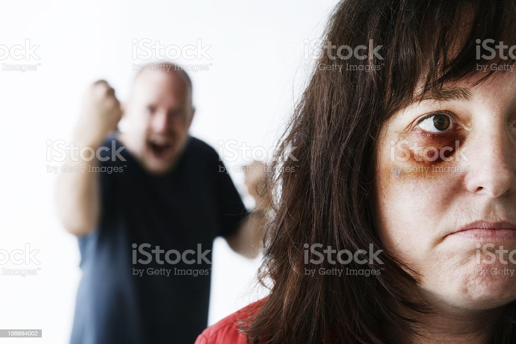 Powerless victim of abuse with bully shaking fist in background stock photo