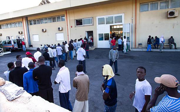 pozzallo, sizilien : afrikanische migranten warten zum frühstück im empfangsbereich - schwarze schlange stock-fotos und bilder