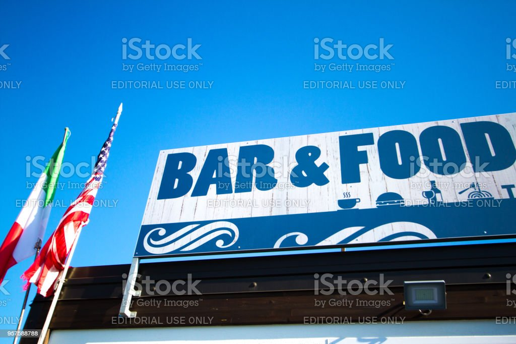 \'Bar and Food\' sign with American and Italian flags hanging nearby....