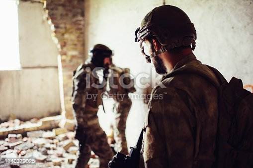 istock A ppicture of soldiers standing in a rooom near ruined wall. Two of them are standing towards each other while thrid one is looking at them. They are having some rest. 1140379025
