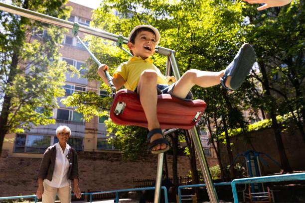 ppy kinder im freien spielen im park - kind schaukel stock-fotos und bilder