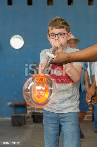 This boy is trying the art of glass blowing in a glass blowing factory in Cabo San Lucas, Mexico.  This factory is a common spot for tourist visits and the professional glass blowers like to give tourists a try at blowing up a glass bubble.  This bubble was quickly broken and discarded after the fun was over.
