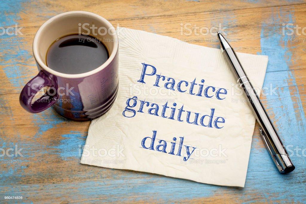 Practice gratitude daily - reminder on napkin stock photo