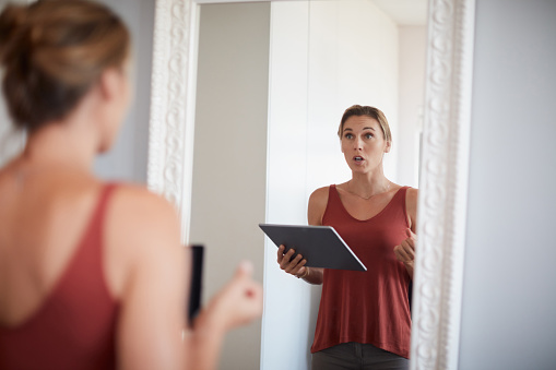 Cropped shot of an attractive young woman having a rehearsal in the mirror while holding a digital tablet