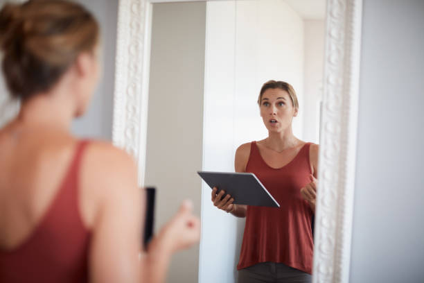 Practice makes perfect Cropped shot of an attractive young woman having a rehearsal in the mirror while holding a digital tablet practicing stock pictures, royalty-free photos & images