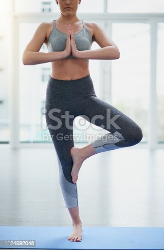 Shot of a young woman practicing yoga in a studio