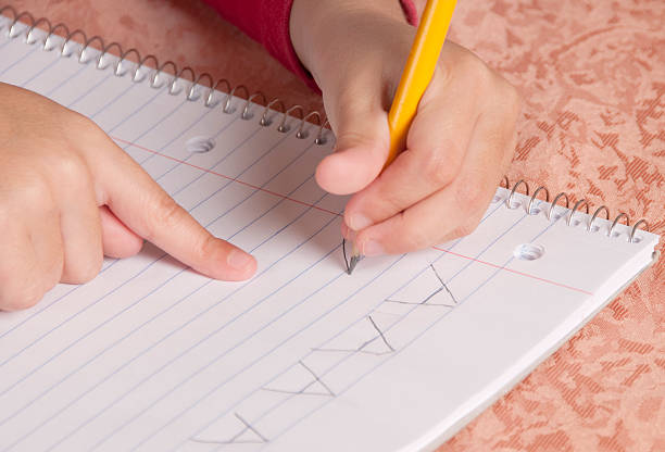 Practicing A Young child writing capital A with a pencil on notebook paper. illiteracy stock pictures, royalty-free photos & images