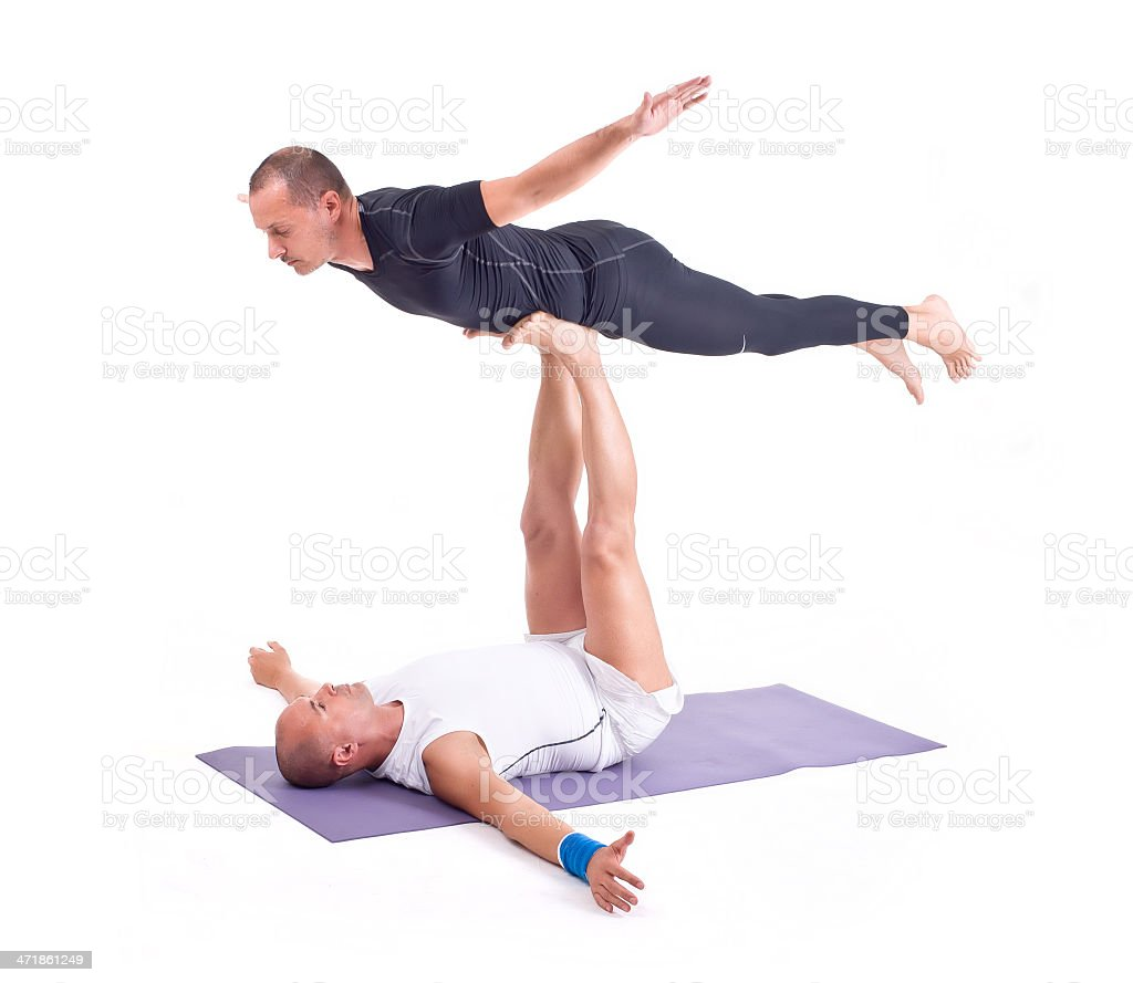 Practicing Acro Yoga exercises in group /  Bird Pose royalty-free stock photo
