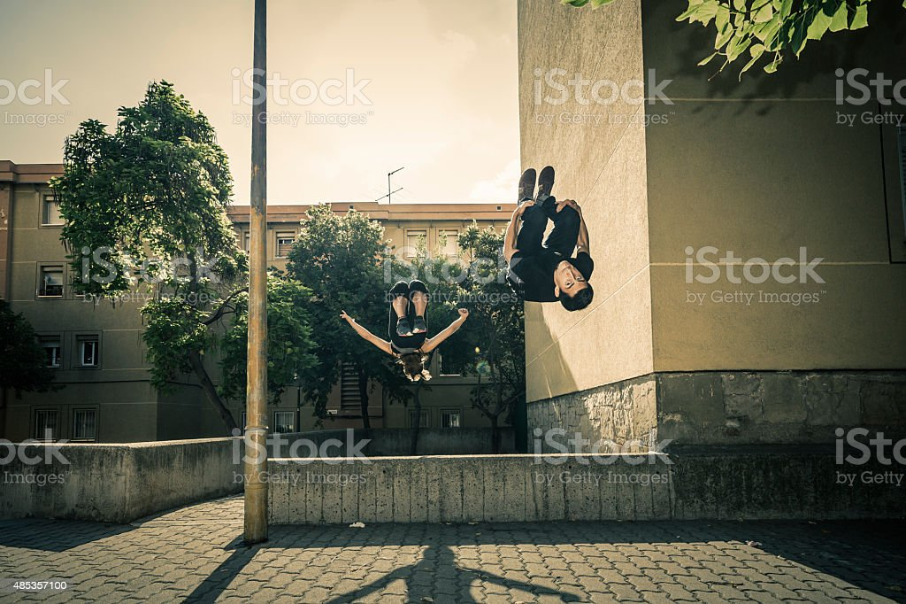 Urban parkour Woman and man doing backflip