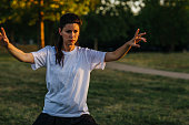 Woman practicing tai chi in public park.