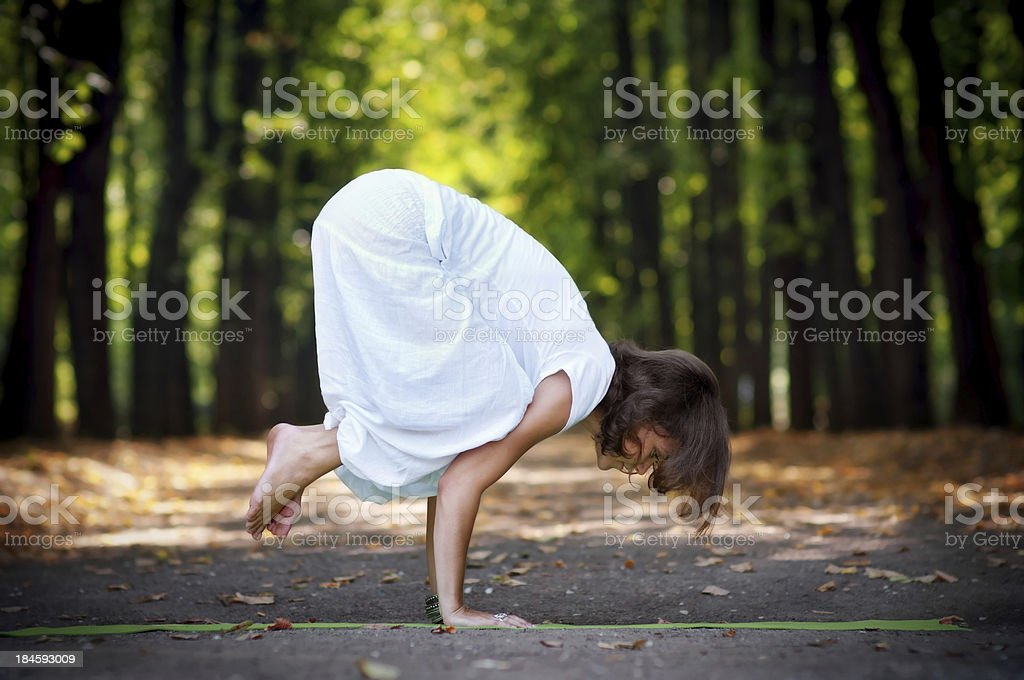 Practicing yoga in the forest, crow pose stock photo