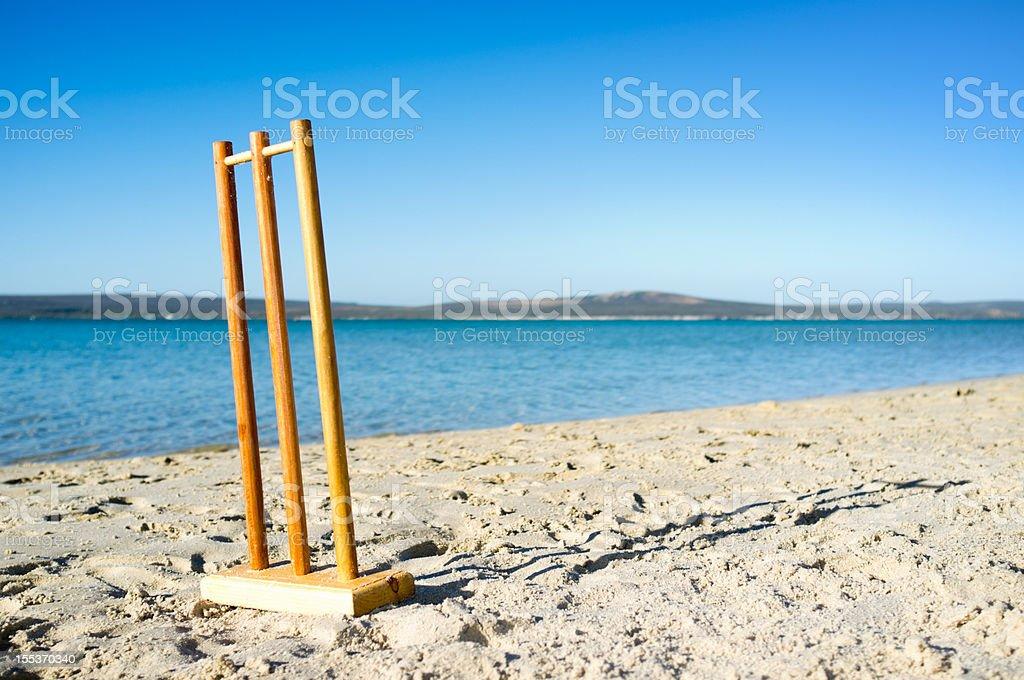 Practise cricket stumps on beach beside beautiful blue lagoon stock photo