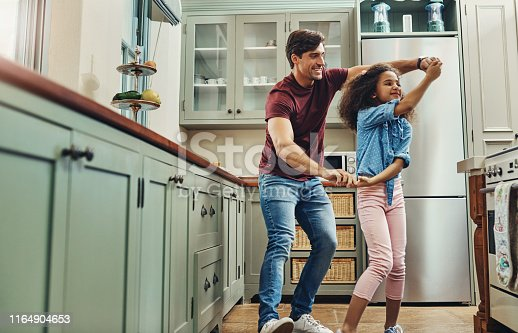 Shot of a young man dancing with his daughter in the kitchen at home