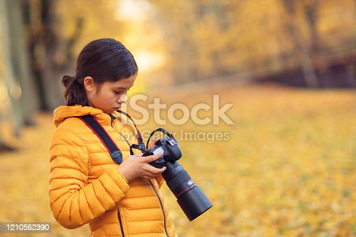 A girl changing the settings of a DSLR camera outdoors in nature.