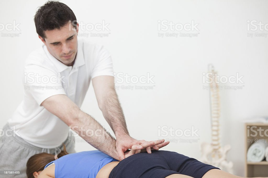 Practitioner pressing the lower back of woman while standing in stock photo