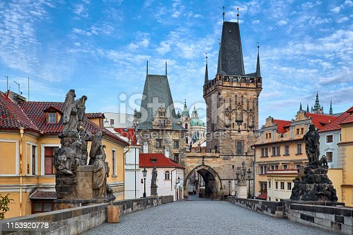 Morning at Charles Bridge in Prague, Czech Republic. Solitary road with statues and paving stones. Antique medieval tower and arch of entrance to the old town Mala Strana district downtown.