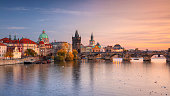 Panoramic cityscape image of famous Charles Bridge in Prague during beautiful autumn sunset.
