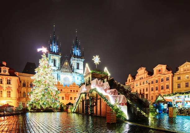 Prague old town square in Christmas decorations at night. Prague old town square in Christmas decorations at night. Unrecognizable people. tyn church stock pictures, royalty-free photos & images