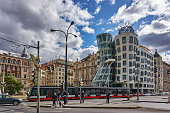 Prague, Czech Republic - September 30, 2019: pedestrians, traffic and a tram on the Rasinovo Nabr. Road. in the background the Dancing House of Prague.