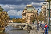 Prague, Czech Republic - September 30, 2019: pedestrians walk along the banks of the Vltava in the direction of Narodni Divadlo.