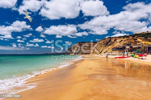 Praia de Porto de Mos with seagulls flying over the beach, Lagos, Portugal. Praia do Porto de Mos, long beach in Lagos, Algarve region, Portugal.