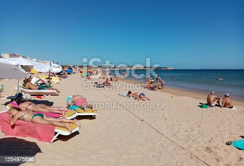 Looking At Building Exterior, People Standing, Looking Around, Swimming, Sunbathing, Sitting Down, Talking To One Another At Portimao Beach In Faro Algarve Portugal Europe